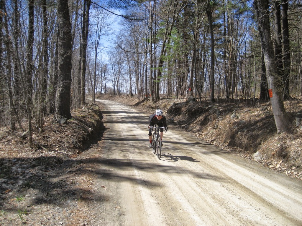 Don riding a dirt road descent.