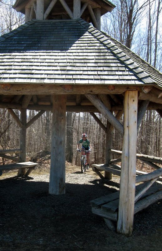 Andy riding up from the woods to a pavilion on the first off-road section.